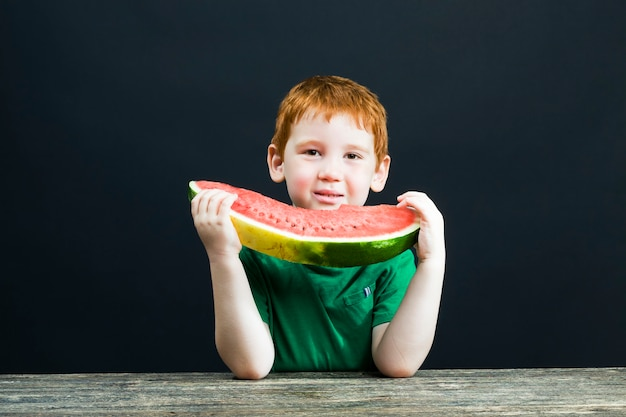 赤い髪の少年は、チャンクにカットされた赤いジューシーなスイカを食べる