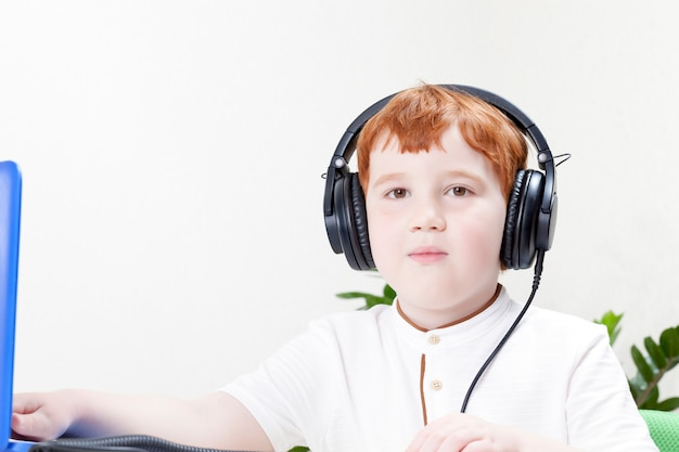 A boy with red hair remotely learns through a computer and the internet