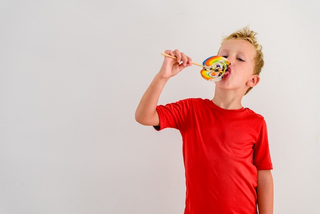 Boy with red shirt on white background eating a lollipop colorful fun and laughing.