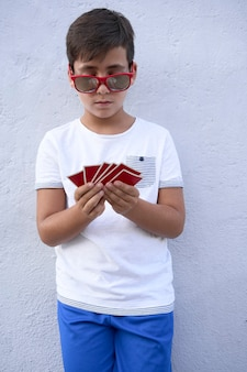 Boy with red sunglasses playing poker
