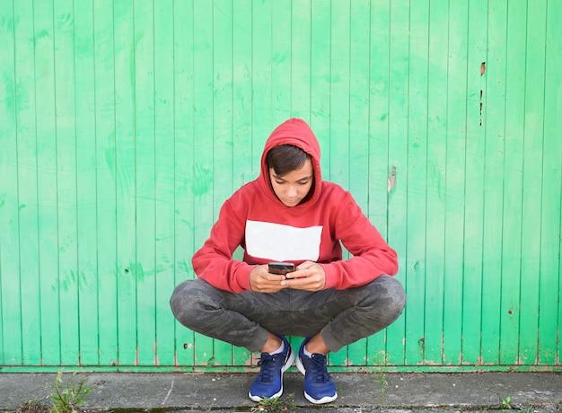 Мальчик с красной толстовкой, занимающейся серфингом со своим смартфоном. зеленый фон