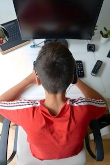 컴퓨터에 빨간 티셔츠를 가진 소년