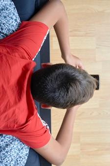 그의 모바일을 사용 하여 빨간 티셔츠를 가진 소년