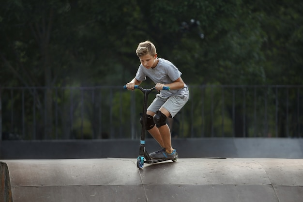 Мальчик со скутером поднимается в воздух в скейт-парке