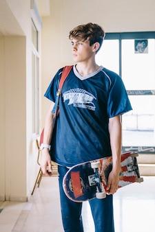 학교 buidling에서 스케이트 보드와 소년