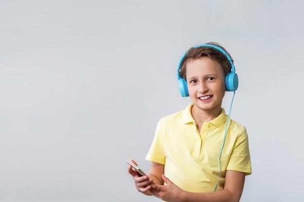 Мальчик с смартфон в руках, слушая музыку в наушниках