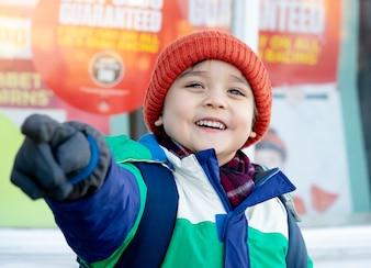 彼の指を指している笑顔を持つ少年