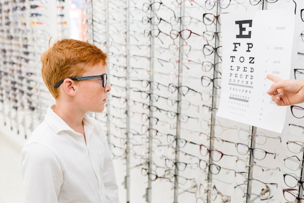 Boy with spectacle looking at snellen chart while doctor's hand pointing at chart