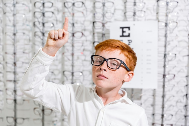 Boy with spectacle pointing at upward direction standing against eyeglasses display background