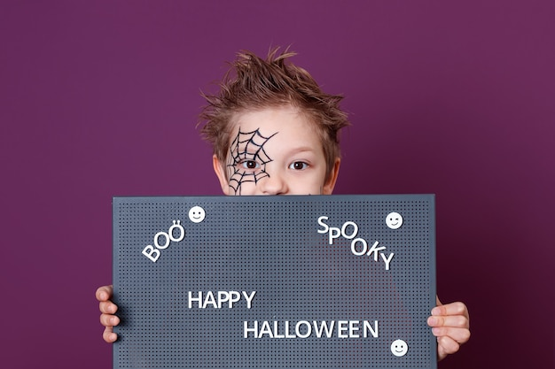 A boy with a spider web drawn on his face, holding a blackboard with the text of halloween. happy halloween. boo. spooky.