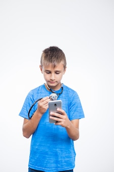 Boy with stethoscope using mobile phone