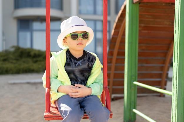 Мальчик с очками в качелях