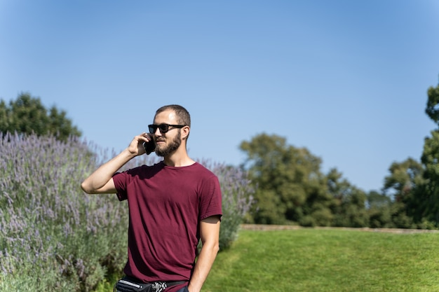 Boy with sunglasses in the middle of a garden talking on a mobile phone