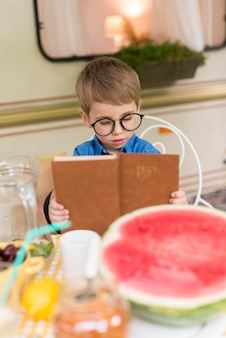Boy with sunglasses reading at the table