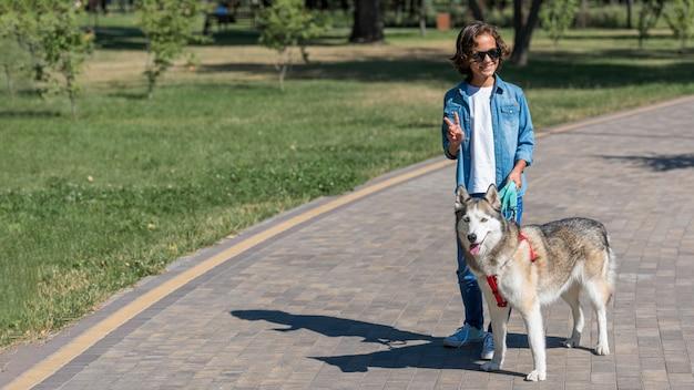 공원에서 그의 개를 산책하는 선글라스와 소년