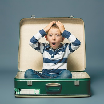 Boy with a surprised expression sitting inside a suitcase