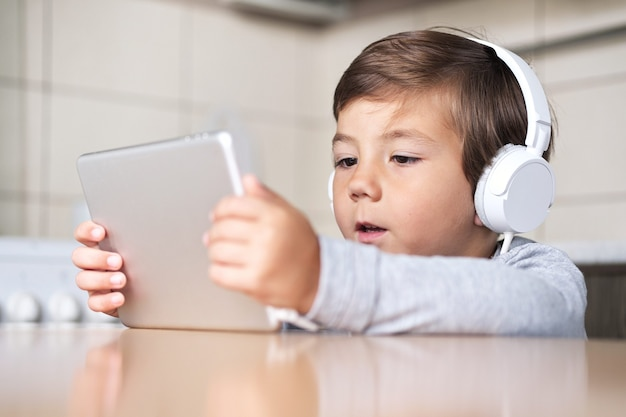A boy with a tablet and headphones sits at the table in the kitchen.