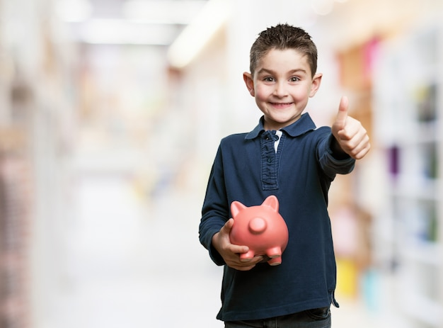 Boy with thumb up and a piggy bank