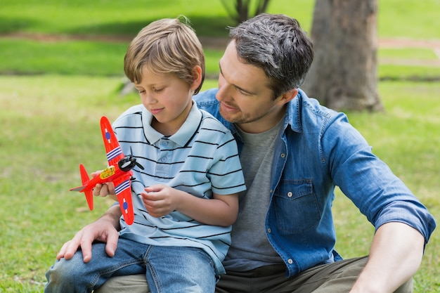Boy with toy aeroplane sitting on father's lap