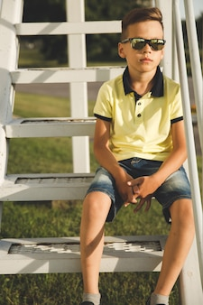 Boy with trendy hairstyle on the stairs wearing sunglasses