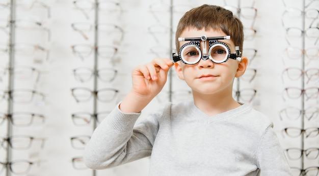 Мальчик с пробной рамкой. пациент малыша для проверки зрения в офтальмологической клинике.