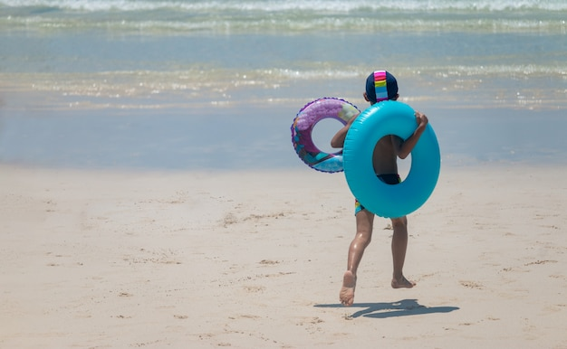 Boy with two swimming rings on the beach