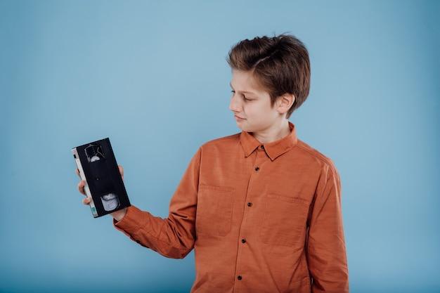 파란색 배경 프로필 보기에 고립 된 비디오 카세트와 소년