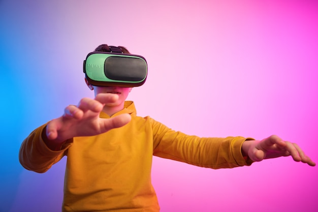Boy with virtual reality glasses on the colorful background. future technology, vr concept