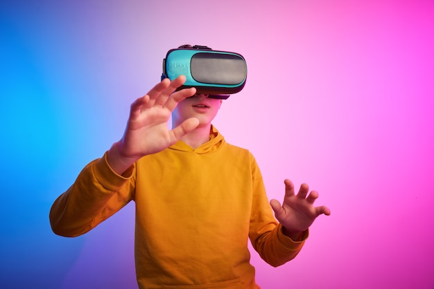 Boy with virtual reality glasses on the colorful wall. future technology, vr concept