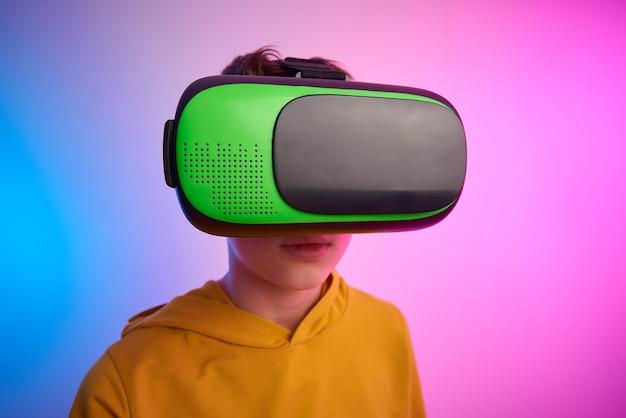 Мальчик с очками виртуальной реальности на красочном фоне. технологии будущего, концепция vr