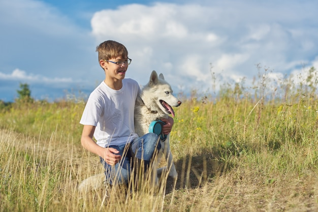Boy with white dog, teenager walking with husky pet