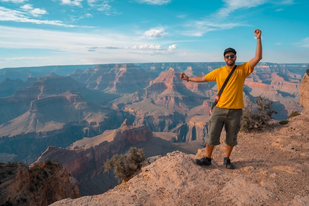 A boy with a yellow shirt at sunset at the mojave point in grand canyon
