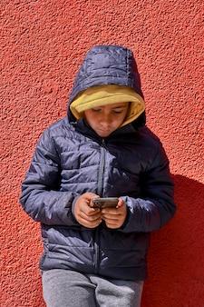 Мальчик с желтой толстовкой, занимающейся серфингом со своим смартфоном. красный фон