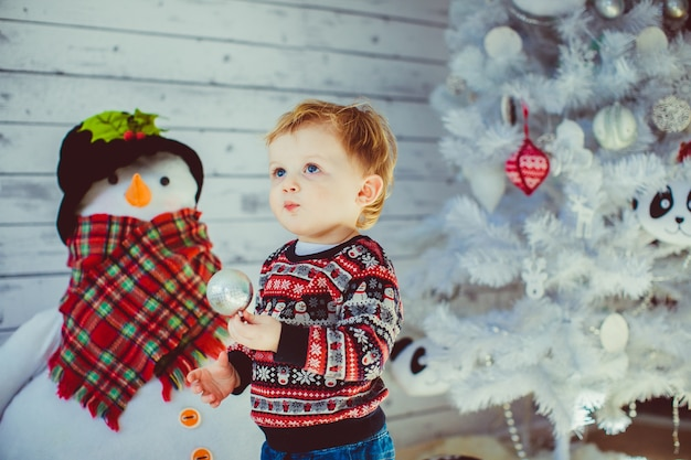 Boy in woolen sweater stands before white christmas tree