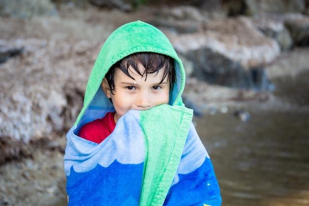 바다에서 수영한 후 수건에 싸인 소년. 여름 해변 휴가 개념. 프랑스의 휴일.