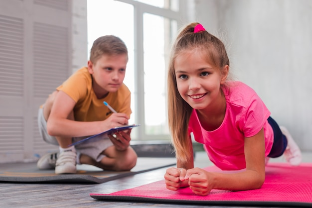 Boy writing on clipboard while looking at smiling girl exercising