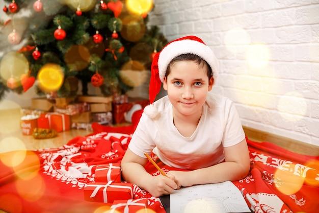 自宅でサンタクロースに手紙を書いている少年子供がサンタクロースに手紙を書いている