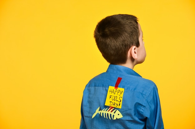 The boy on a yellow background in a blue shirt with a fish glued tape and a piece of paper on his back