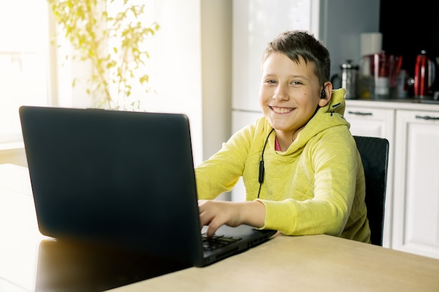 Boy in yellow clothes is watching movie studying or playing game online on computer at home kitchen