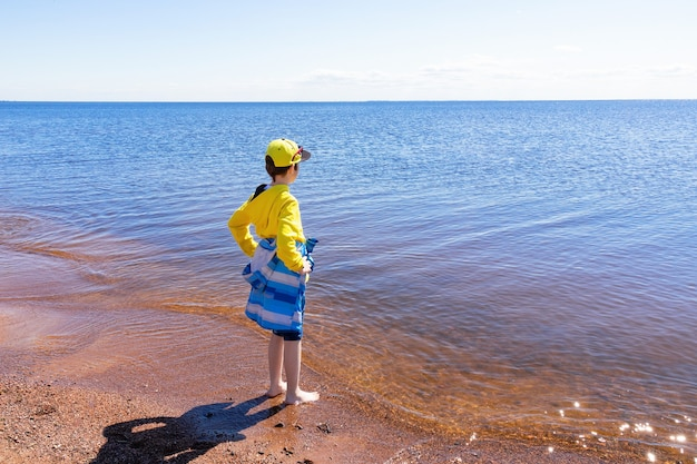 Boy in yellow hoodie and cap, in blue jacket, with rolled up jeans barefoot on the seashore on a sunny day.