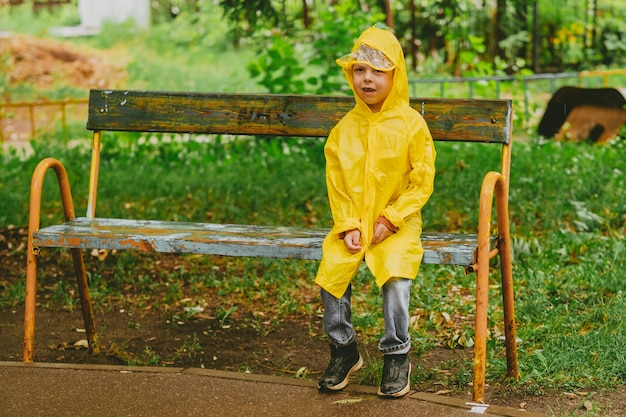A boy in a yellow raincoat sits on a bench in the rain. a lonely child is lost on the street. children without supervision. bright clothes for children for a walk.
