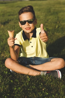 A boy in a yellow t-shirt sits on the grass and eats ice cream. asian appearance