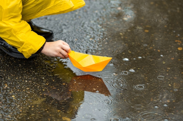 Boy in yellow waterproof cloak and black rubber boots playing with paper handmade boat toy in a puddle outdoors in the rain in autumn.