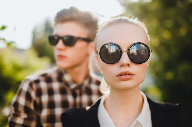 Boy and young girl with sunglasses and a park background