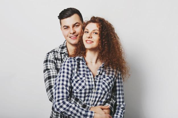ガールフレンドとboyfreindは情熱的に抱きしめ、幸せな表情を持ち、良い感情を示し、白い壁に孤立しています。素敵な巻き毛の女性は彼女の恋人の屋内で休む