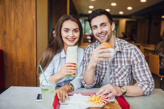 Парень и девушка едят гамбургер