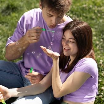 Парень и девушка играют с мыльными пузырями