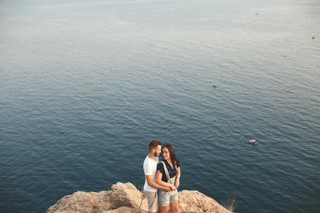 Парень и девушка сидят на скале