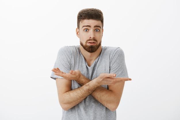 Сбитый с толку парень не может понять, что сделал не так. невежественный и сомнительный очаровательный брюнет с бородой и голубыми глазами, пожимая плечами, скрестив руки, открыв рот, встревоженно стоит над серой стеной