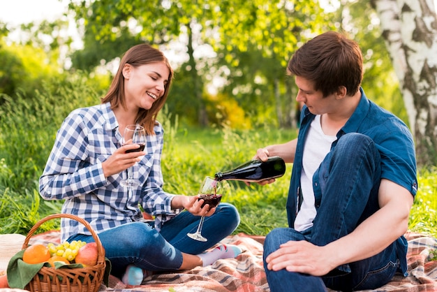 Boyfriend filling glasses held by girlfriend with wine